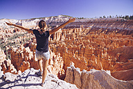 USA, Utah, young female tourist looking down to the Hoodoo rock formations in Bryce Canyon National Park - MBEF000834