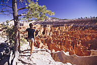 USA, Utah, young female tourist looking down to the Hoodoo rock formations in Bryce Canyon National Park - MBEF000836