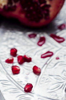 Pomegranate [Punica granatum] and pits on silver tray, close-up - CZ000113