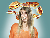 Disgusted young woman with flying fast food around her head, Composite - STKF000502