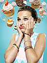 Young woman with flying cupcakes around her head, Composite - STKF000500