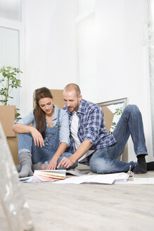 Young couple moving into new home, looking at color sample - FKF000323