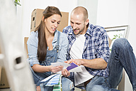 Young couple moving into new home, looking at color sample - FKF000325
