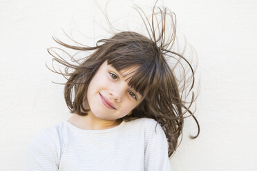 Portrait of smiling little girl with wafting hair - LV000320