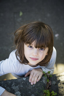 Portrait of little girl climbing on a wall - LV000319