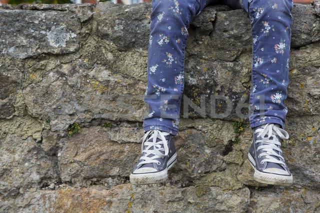 Legs of little girl sitting on a wall - LVF000321