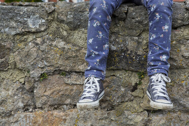 Legs of little girl sitting on a wall - LVF000321
