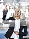 Portrait of business woman drawing red line on glass panel - STKF000531