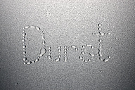 Water drops on metal sheet, forming word thirst - STKF000560