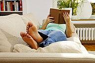 Woman lying on couch reading book - HOH000255
