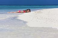Maldives, Young woman in bikini lying in shallow water - AMF001211