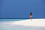 Maldives, Young woman in bikini walking on beach - AMF001209
