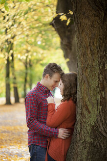 Young couple leaning against tree trunk - BGF000019