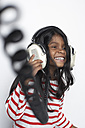 Portrait of smiling girl hearing music with headphones - FSF000305