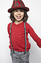Portrait of smiling little boy with wooden rattle wearing hat and suspenders - FSF000312