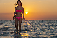 Maledives, young woman walking in water - AMF001242