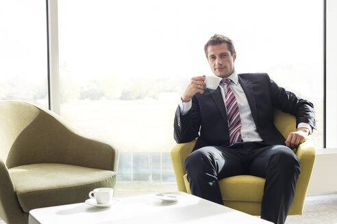 Poland, Warzawa, businessman having a coffee break at hotel lounge - MLF000284