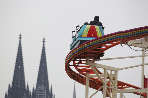 Germany, North Rhine-Westphalia, Cologne, Roller coaster at fairground, in the background Cologne Cathedral - JAT000445