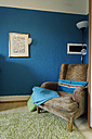 Wing chair standing in a corner of a living room in front of blue coloured wall - LB000498