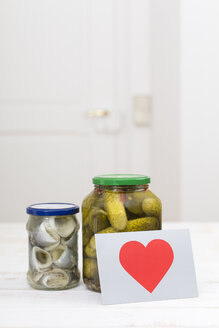 Glass of pickled cucumbers, a glass of rollmops and a postcard with red heart on white wooden table - DRF000282