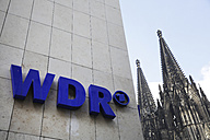 House facade with logo of WDR (Westdeutscher Rundfunk, West German Broadcasting), part of Cologne Cathedral at background - JAT000505