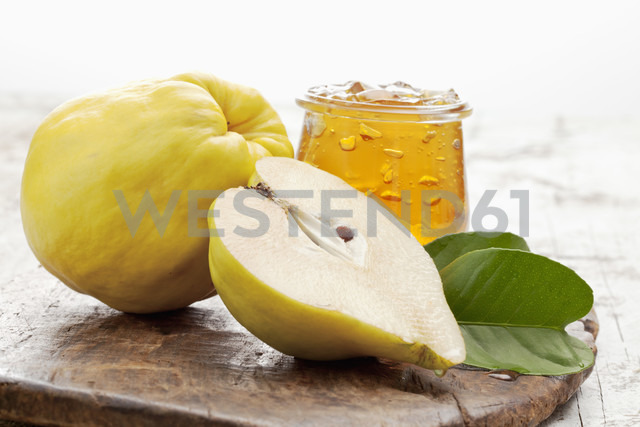 One and a half quince (Cydonia oblonga) and a glass of quince marmalade on wooden board - CSF020324 - Dieter Heinemann/Westend61