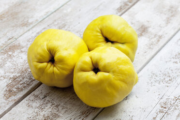 Three quinces (Cydonia oblonga) on wooden table - CSF020327
