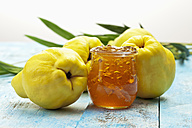 Four quinces (Cydonia oblonga), a spoon and a glass of quince marmalade on wooden table - CSF020323