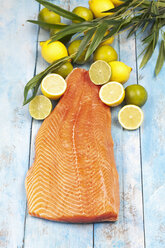 Salmon fillet (Salmo salar) and lemons on blue wooden table - CSF020334