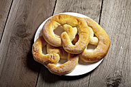 Three sugar pretzels and a plate on wooden table - CSF020343
