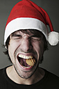 Young man with Santa hat trying to crack a walnut with his teeth, studio shot - JATF000517