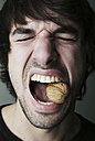 Portrait of young man trying to crack a walnut with his teeth, studio shot - JATF000514