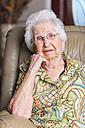 Aged woman sitting in an armchair - ABAF001066