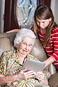 Aged woman and her great-granddaughter looking at tablet computer - ABAF001068
