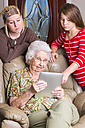 sAged woman and two great-granddaughters looking at tablet computer - ABAF001083