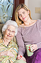 Aged woman and her great-granddaughter sitting side by side - ABAF001065