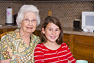 Aged woman and her great-granddaughter sitting side by side - ABAF001075