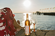 Germany, Bavaria, Nonnenhorn, Woman with wine on the bank of Lake Constance - SH001023