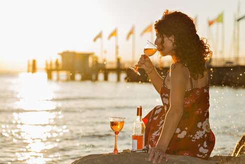 Germany, Bavaria, Nonnenhorn, Woman with wine on the bank of Lake Constance - SH001026