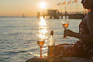Germany, Bavaria, Nonnenhorn, Woman with wine on the bank of Lake Constance - SH001025