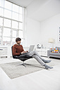 Germany, Munich, Man using laptop at home - RBF001415