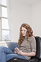 Germany, Munich, Woman at home, sitting in chair, using digital tablet - RBF001440