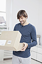 Germany, Munich, Man unpacking cardboard box - RBF001474