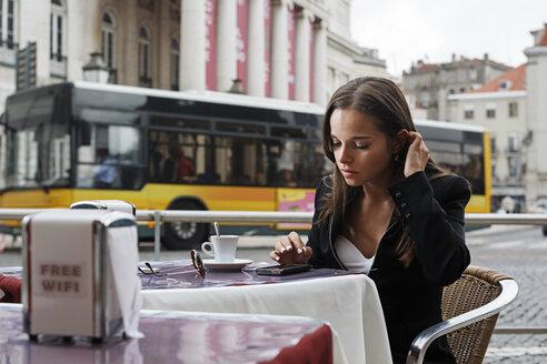 Portugal, Lisboa, Baixa, Rossio, Praca Dom Pedro IV, Teatro Nacional, young woman using smart phone sitting at street cafe - BIF000045