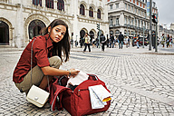 Portugal, Lisboa, Baixa, Rossio, desperating young woman with city map and travel bag - BIF000052