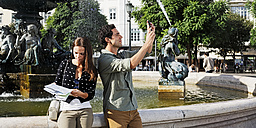 Portugal, Lisboa, Baixa, Rossio, Praca Dom Pedro IV, young couple with city map and smart phone in front of a fountain - BIF000041
