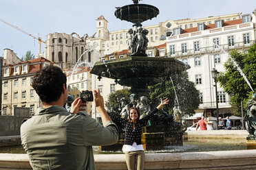 Portugal, Lisboa, Baixa, Rossio, Praca Dom Pedro IV, young couple photographing in front of a fountain - BIF000039