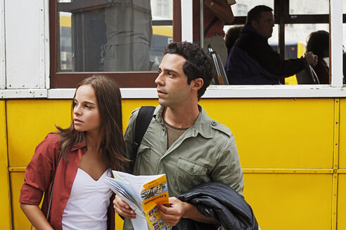 Portugal, Lisboa, Baixa, Rossio, young couple with city map in front of tram - BIF000063