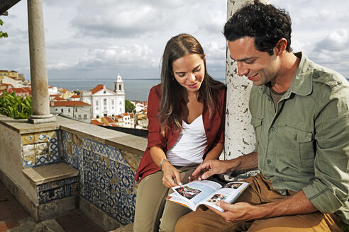 Portugal, Lisboa, Alfama, Miradouro de Santa Luzia, young couple with guidebook - BI000032