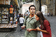 Portugal, Lisboa, Baixa, Rossio, young couple looking at postcard - BIF000022